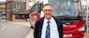 man smiles infront of bus